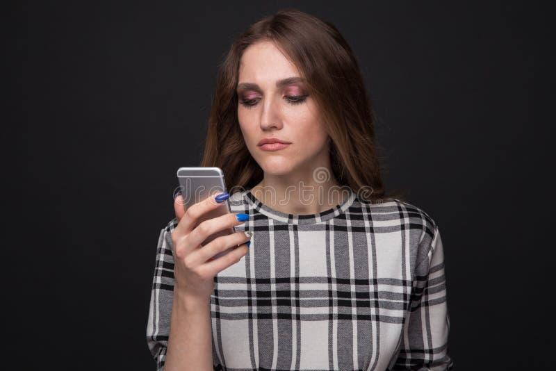 Essere teenager triste vittima del cyberbullismo online che si siede su uno strato nel salone a fotografia stock libera da diritti