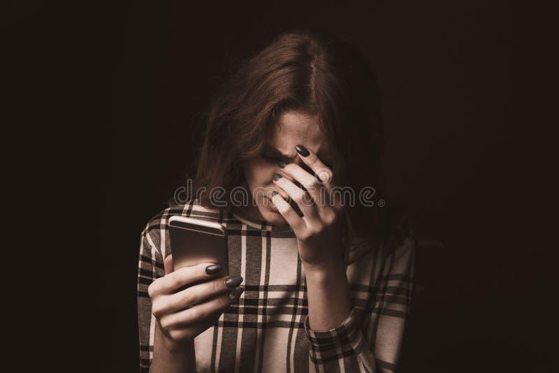 Essere teenager triste vittima del cyberbullismo online che si siede su uno strato nel salone a fotografie stock libere da diritti