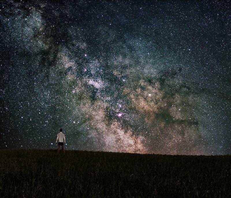 Essere umano che guarda al centro della galassia della Via Lattea fotografia stock