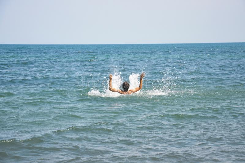 Essere umano d'affondamento nel mare fotografie stock