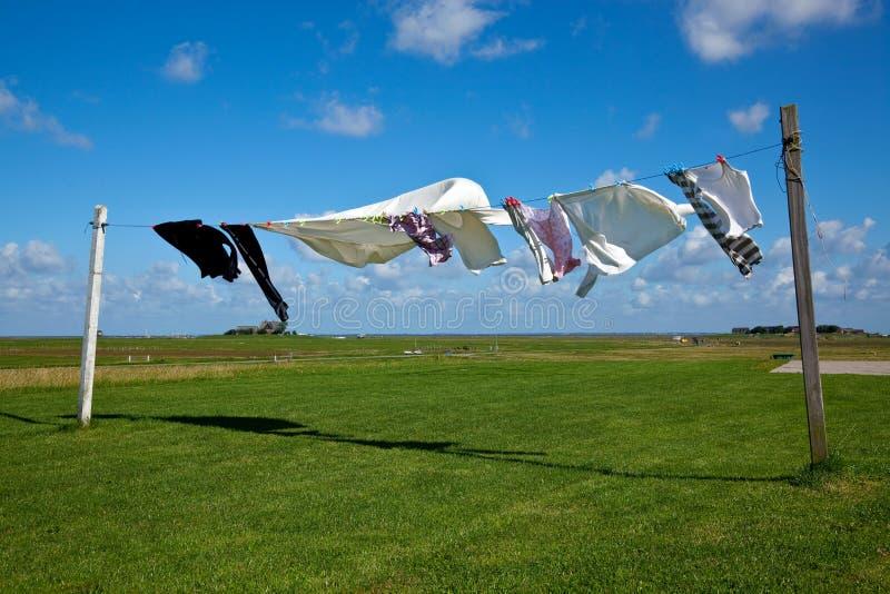 Essiccamento della lavanderia sulla riga di vestiti contro un cielo blu fotografia stock