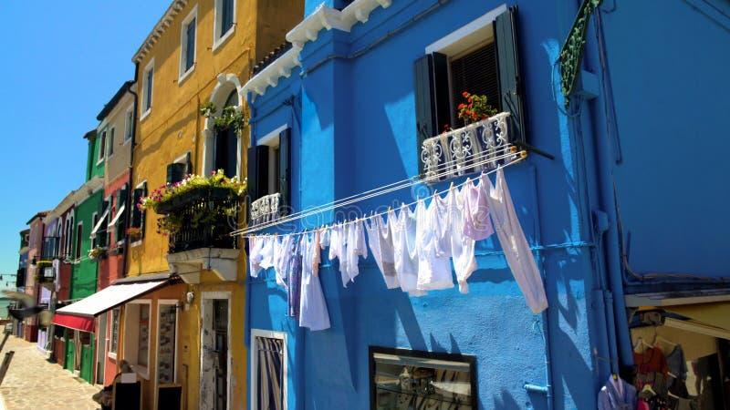 Essiccazione bianca della lavanderia sulla facciata blu della casa, via dell'isola di Burano, vita in Italia fotografia stock