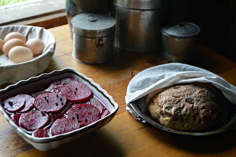 In Essig eingelegte rote Rüben, Kapriolen, Kartoffel-Brot, frische Eier stockfotografie