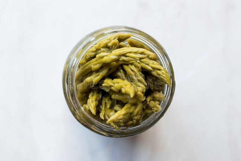 In Essig eingelegter grüner Spargel legt gegoren und im Glasflaschen-Glas konserviert in Essig ein lizenzfreie stockfotografie