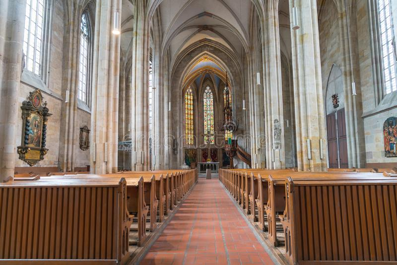 Long aisle between rows of pews to altar. ESSLINGEN GERMANY - SEPTEMBER 13 2017; Long aisle between rows of pews to altar and stained glass windows inside stock photos