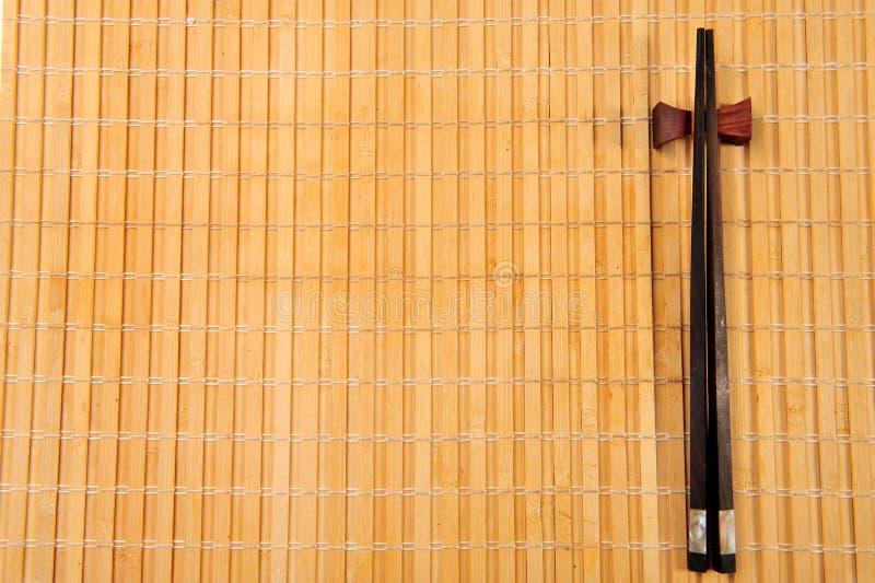 Essstäbchen auf einer Bambusmatte lizenzfreie stockfotos