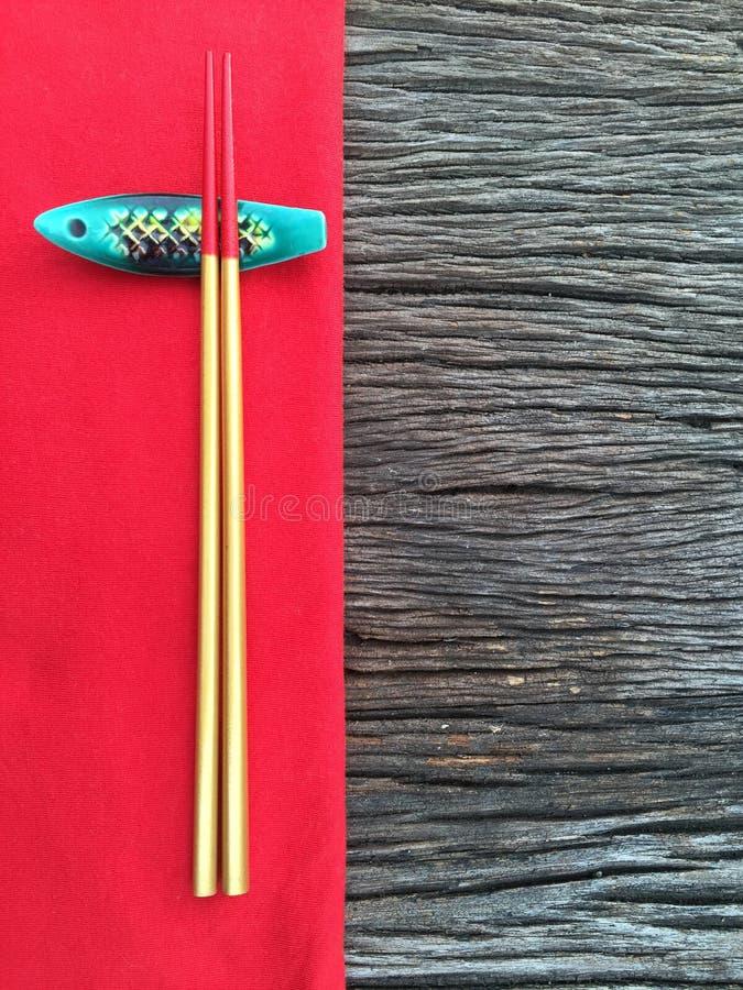 Essstäbchen auf hölzerner und roter Tischdecke lizenzfreie stockbilder