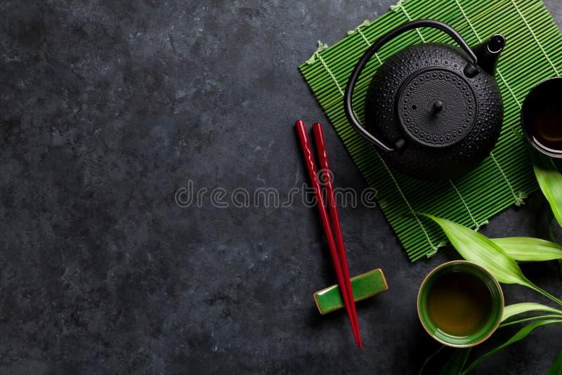 Essstäbchen des grünen Tees und der Sushi stockfotografie