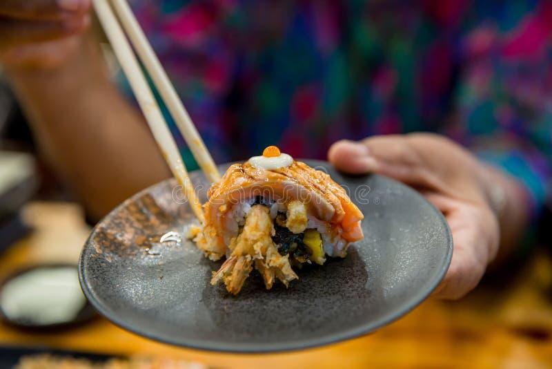 Essstäbchen halten auf frischen Lachsen der Sushi Japanisches Lebensmittel f?r gesundes Lachssushi, erstklassiges Menü der Eilach stockbilder