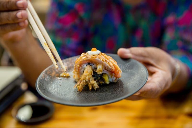 Essstäbchen halten auf frischen Lachsen der Sushi Japanisches Lebensmittel f?r gesundes Lachssushi, erstklassiges Menü der Eilach lizenzfreies stockbild