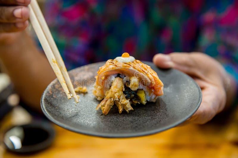 Essstäbchen halten auf frischen Lachsen der Sushi Japanisches Lebensmittel f?r gesundes Lachssushi, erstklassiges Menü der Eilach lizenzfreies stockfoto