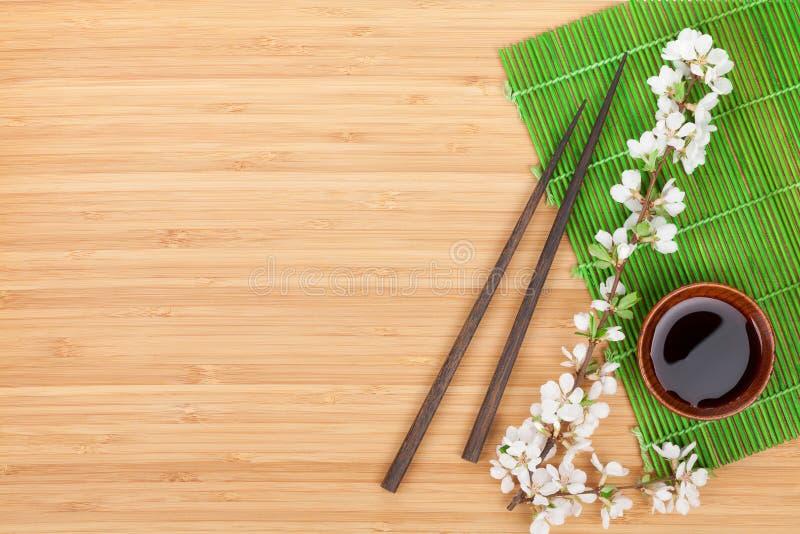 Essstäbchen, Kirschblüte-Niederlassung, Sojasoße und Bambusmatte lizenzfreies stockbild