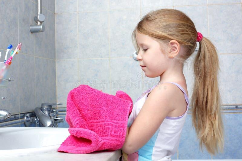 Essuie-main pris par fille après lavage dans la salle de bains photo stock