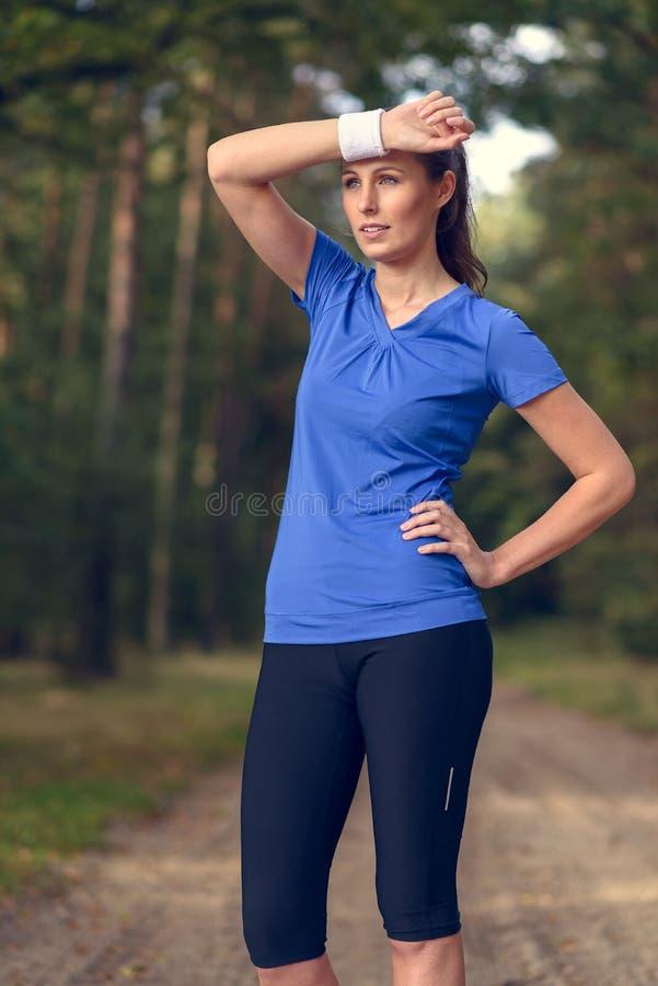 Essuyage d'athlète de femme sué de son front photo stock