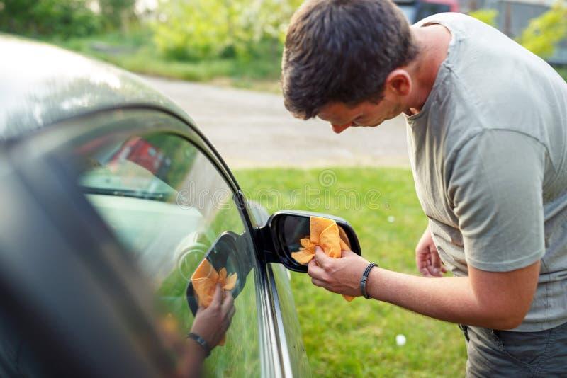 Essuyage de la voiture automobile de nettoyage d'homme avec le tissu de microfiber, detailin de voiture photos stock