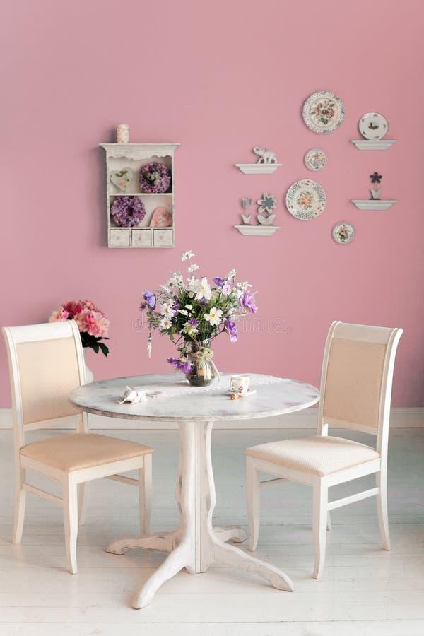 Esszimmerinnenraum mit der rosa Wand der dekorativen Platten der Blumen stockfoto