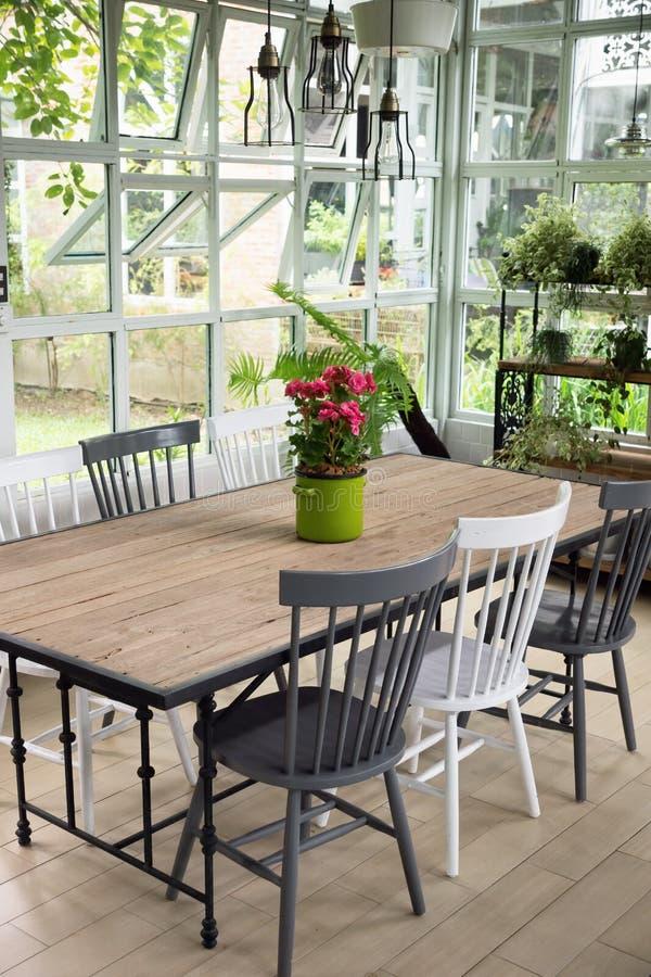 Esszimmerinnenraum mit Tabelle, Stühlen und Anlagen gegen großes w stockfotografie