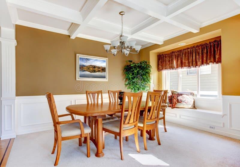 Esszimmerinnenraum mit weißer Bank- und Holztabelle. stockfotografie