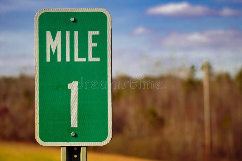 Está aqui um sinal de 1 milha na estrada foto de stock