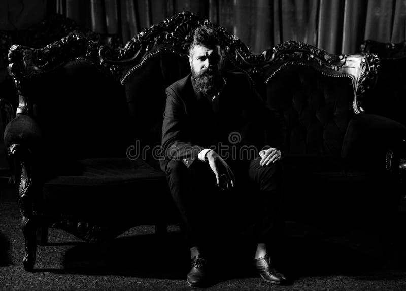Está sentando-se em um sofá de couro em um interior luxuoso Retrato de um homem maduro considerável imagem de stock