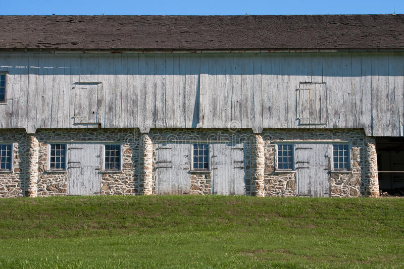 Estábulos coloniais do cavalo da pedra e da madeira fotografia de stock