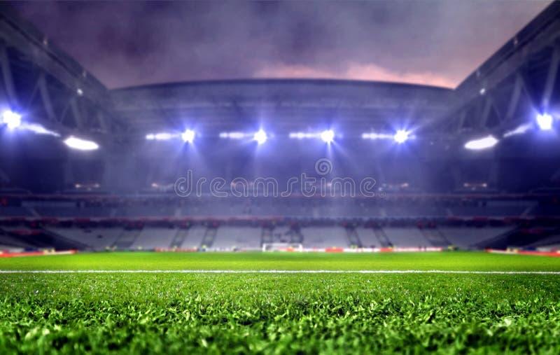 Estádio com campo de futebol e projetores brilhantes na noite fotografia de stock
