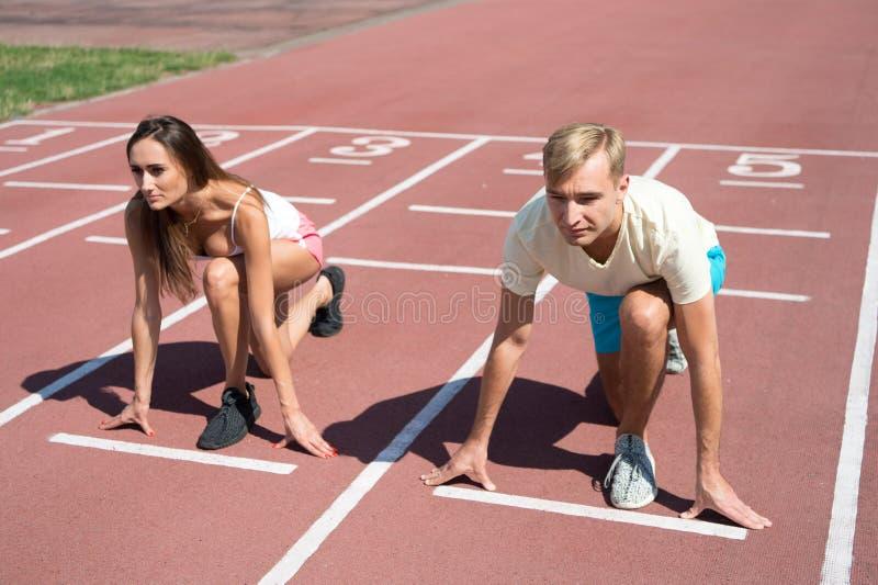 Estádio da superfície running de posição de começo do homem e da mulher baixo Competição ou raça running do gênero Um desportista fotos de stock