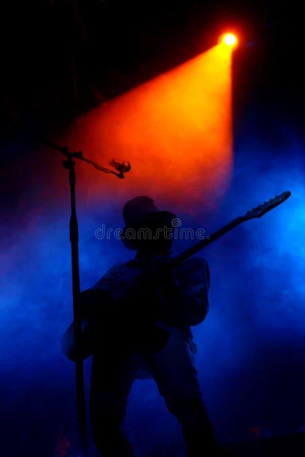 Estágio com o jogador do fumo e de guitarra imagens de stock