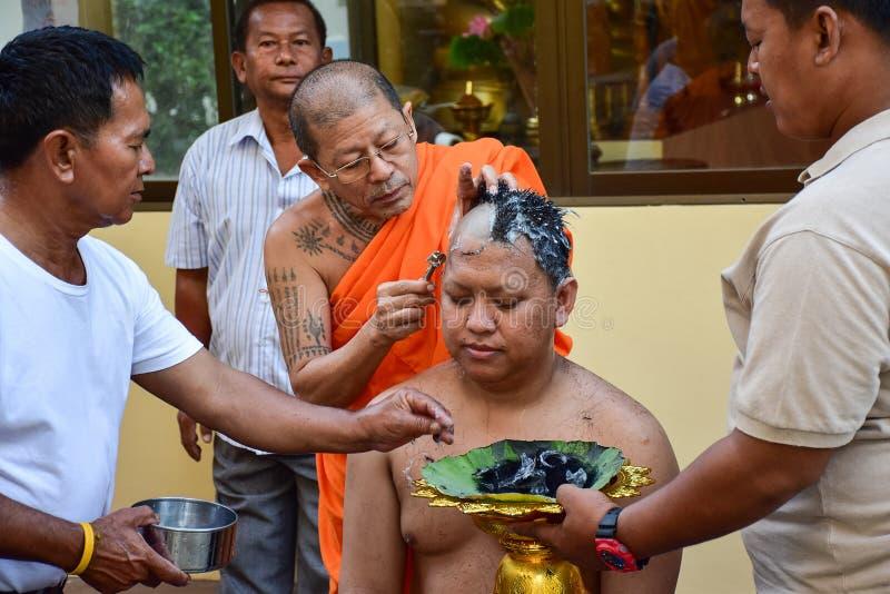 Están afeitando su cabeza en ceremonia de la ordenación y él hará un monje en budismo fotos de archivo