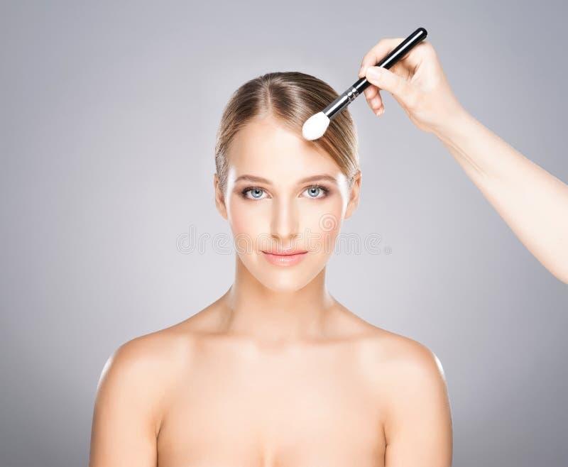 Están aplicando a la muchacha hermosa con los cosméticos foto de archivo libre de regalías