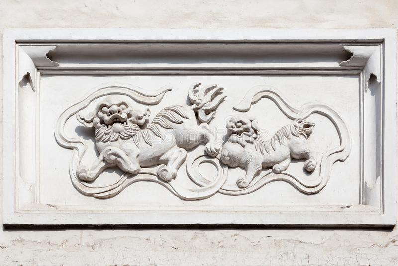 Estátua antiga do granito de criaturas chinesas mitológicas Qilin em um tijolo e em um muro de cimento do estilo antigo foto de stock