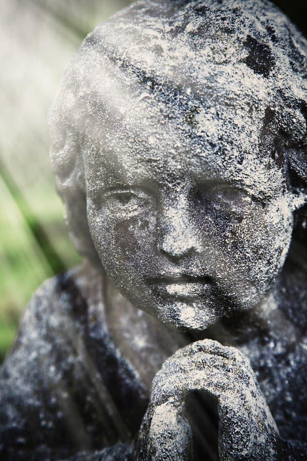 Estátua antiga do guardião do anjo nos raios da fé da luz, com referência a imagens de stock