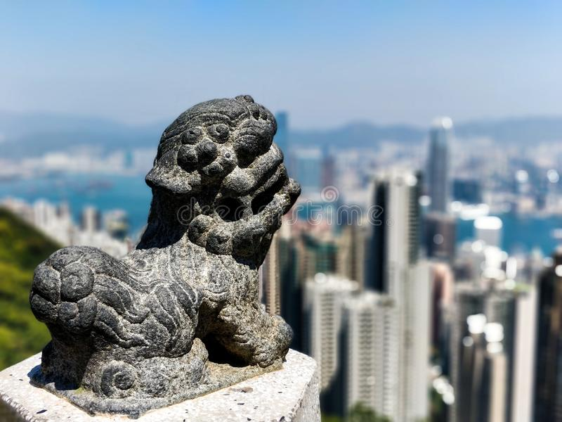 Estátua asiática com a skyline de Hong Kong borrada no fundo fotografia de stock royalty free