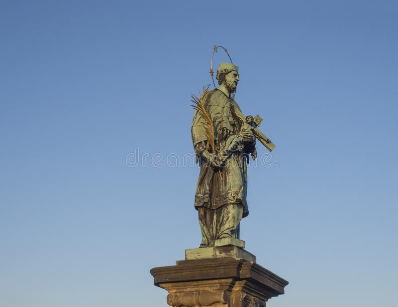 Estátua barroco de Saint John de Nepomuk com o crucifixo dourado da terra arrendada do halo da estrela com Jesus Christ em Charle imagens de stock