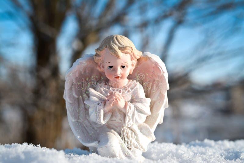 Estátua com um fundo do céu azul, tempo do anjo da criança de inverno foto de stock