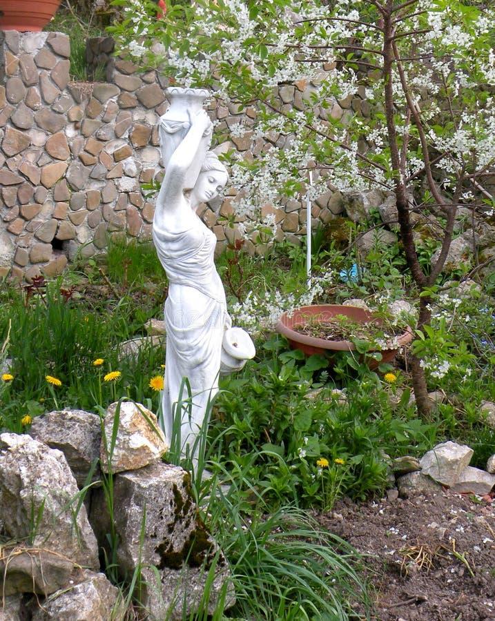Estátua como a decoração Flores no jardim em um dia ensolarado foto de stock
