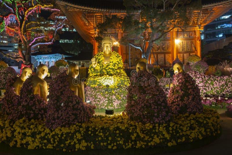 Estátua da Buda com flores coloridas foto de stock royalty free