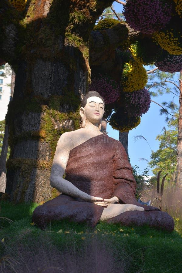 Estátua da Buda com flores coloridas imagens de stock royalty free