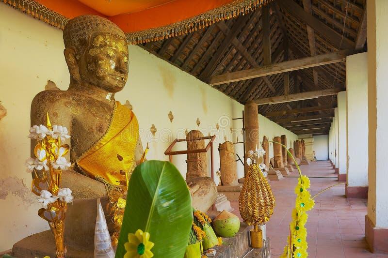 Estátua da Buda com ofertas frescas nesse Luang Stupa em Vientiane, Laos fotos de stock royalty free