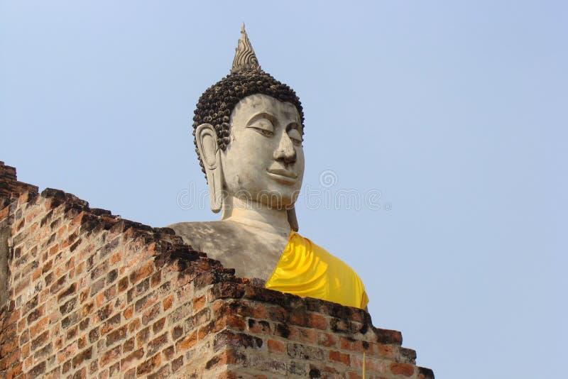 Estátua da Buda com a veste amarela em Ayutthaya, Tailândia imagens de stock royalty free