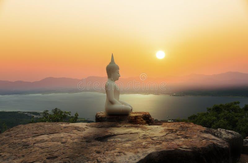 Estátua da Buda na montanha com por do sol ou nascer do sol fotos de stock