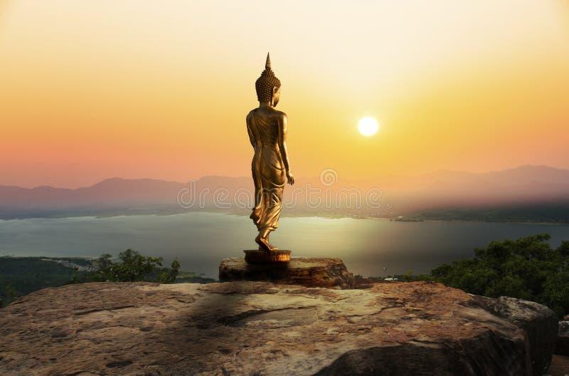 Estátua da Buda na montanha com por do sol ou nascer do sol imagens de stock