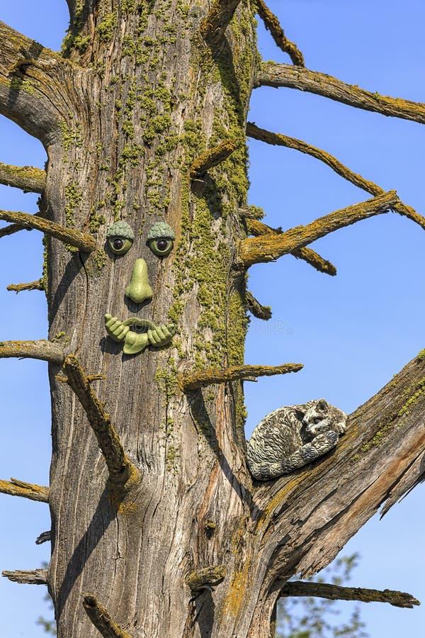 Estátua da cara e do gato na árvore imagem de stock royalty free