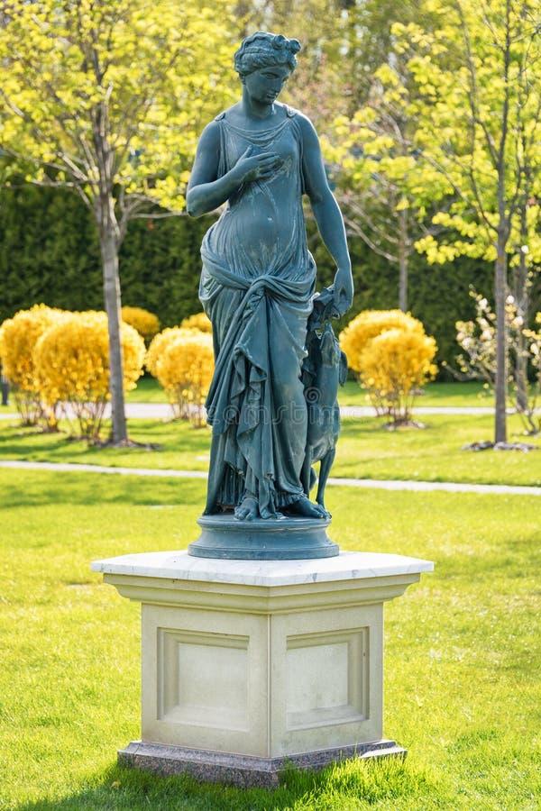 Estátua da deusa em um estilo clássico Estátua esquisito da ninfa com o cão no parque fotos de stock