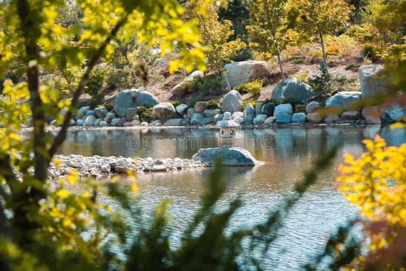Estátua da lanterna japonesa quadro por árvores e por arbustos imagem de stock royalty free