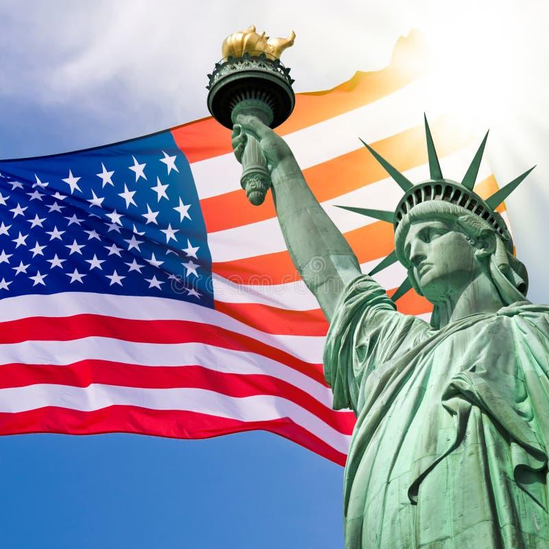 Estátua da liberdade, céu ensolarado e bandeira dos EUA fotos de stock