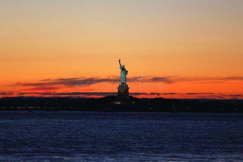 A estátua da liberdade no porto de New York no por do sol imagens de stock royalty free