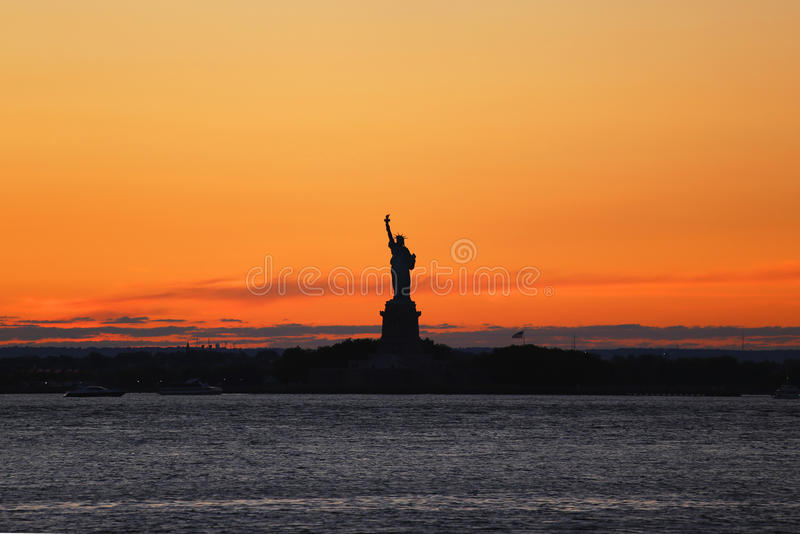 A estátua da liberdade no porto de New York no por do sol imagem de stock