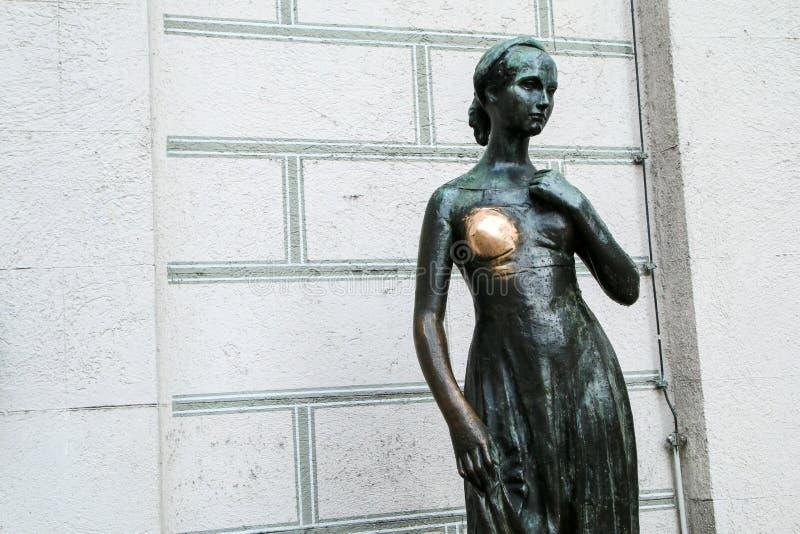 A estátua da mulher com para fora um peito gasto fotografia de stock royalty free