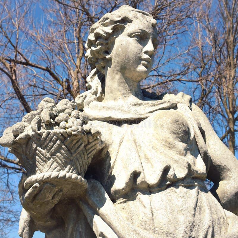 Estátua da mulher que guarda a cesta do fruto fotos de stock royalty free